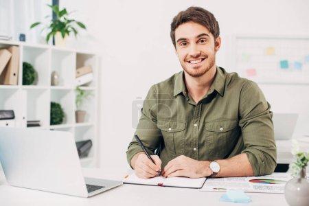 Photo pour Jeune homme d'affaires souriant et tenant stylo dans le bureau moderne - image libre de droit