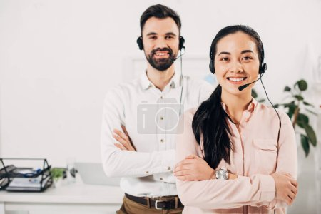 Selective focus of female manager smiling with crossed arms while male coworker standing behind with headset