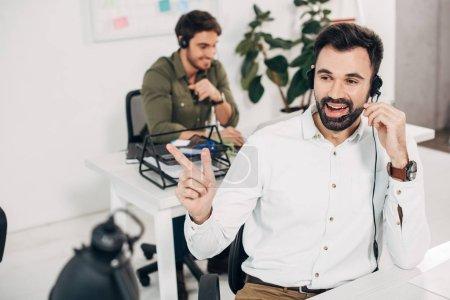 Foto de Operador masculino alegre usando auriculares y hablando en el centro de llamadas - Imagen libre de derechos