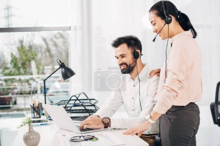 Smiling female manager putting hand on shoulder of male coworker and looking at laptop