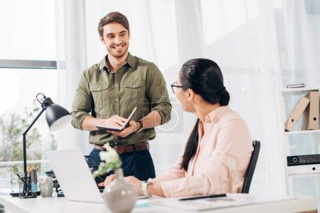 Photo pour Gestionnaire de mâle regardant femelle collaborateur dans le bureau moderne - image libre de droit