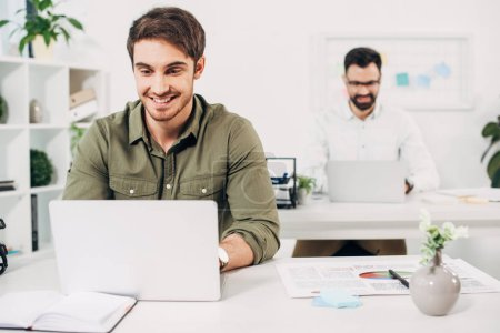 Selective focus of cheerful manager using laptop with coworker on background
