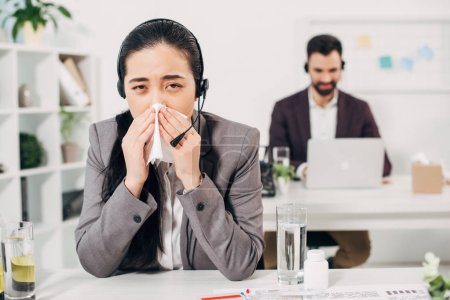 Sick female manager blowing nose and sitting in headset in call centre