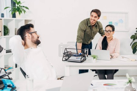 Coworkers looking at colleague and smiling in office