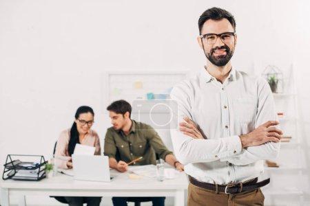 Photo pour Mise au point sélective du gestionnaire debout avec les bras croisés avec des collègues sur fond de - image libre de droit