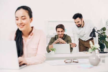 Photo for Selective focus of male coworkers looking at laptop and smiling in office - Royalty Free Image