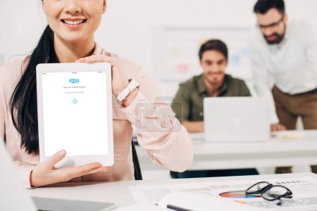 Photo pour Recadrée vue du gestionnaire de femme souriant montrant une tablette numérique avec Skype app - image libre de droit