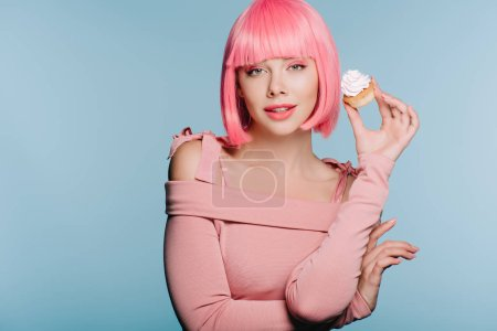 Photo for Beautiful happy girl in pink wig posing with delicious cupcake isolated on blue - Royalty Free Image