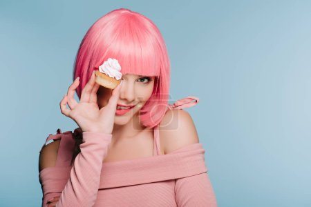 Photo for Attractive smiling girl in pink wig holding cupcake isolated on blue - Royalty Free Image
