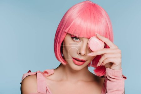 Photo for Attractive girl in pink wig posing with macaron isolated on blue - Royalty Free Image