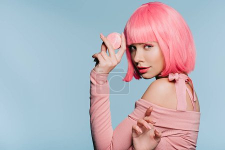 attractive girl in pink wig posing with sweet macaron isolated on blue
