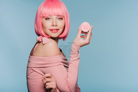 beautiful girl in pink wig posing with tasty macaron isolated on blue
