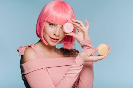 fashionable girl in pink wig posing with two macarons isolated on blue