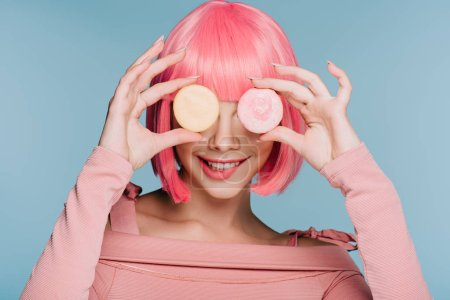 attractive smiling girl in pink wig posing with two macarons isolated on blue
