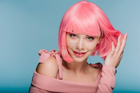 fashionable sensual girl posing in pink wig isolated on blue