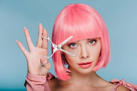 Foto de Chica atractiva moda en rosa peluca con tijeras aisladas en azul - Imagen libre de derechos