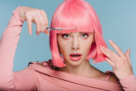 Foto de Dado una sacudida eléctrica chica elegante corte de cabello rosado con tijeras aisladas en azul - Imagen libre de derechos