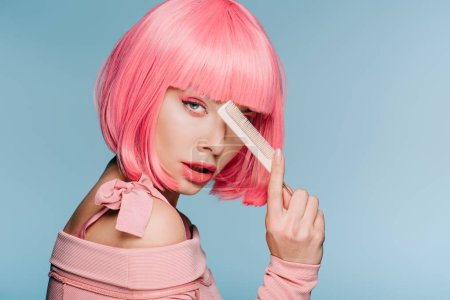 beautiful stylish girl in pink wig posing with hair comb isolated on blue