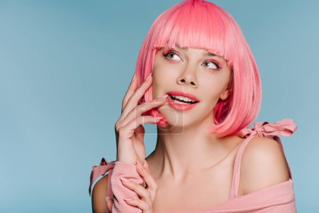 Photo for Beautiful dreamy girl posing in pink wig isolated on blue - Royalty Free Image
