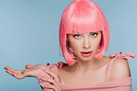 Photo pour Belle fille choquée en perruque rose posant avec haussement d'épaules geste isolé sur bleu - image libre de droit