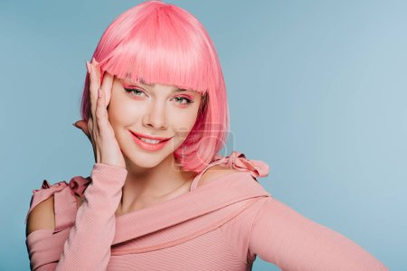 Photo for Stylish smiling girl posing in pink wig isolated on blue - Royalty Free Image