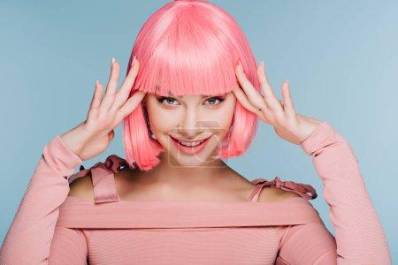 Photo pour Joyeuse fille à la mode gesticulant et posant dans une perruque rose isolée sur bleu - image libre de droit