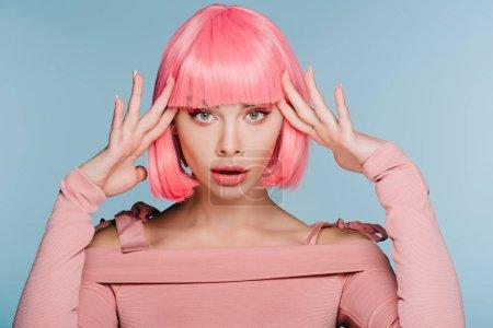 Photo pour Jolie fille choquée gesticulant et posant dans une perruque rose isolée sur bleu - image libre de droit