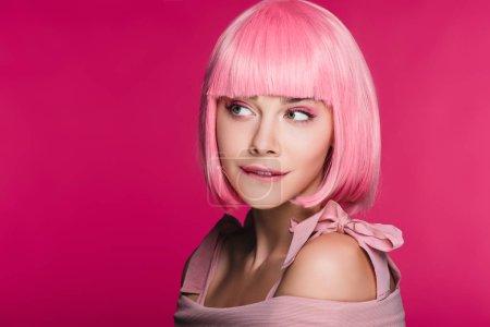 belle femme sensuelle en perruque rose mord la lèvre, isolée sur pink