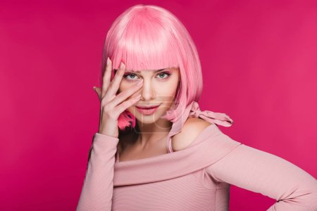 beautiful young woman gesturing and posing in pink wig, isolated on pink