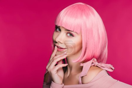 fashionable young woman posing in pink wig, isolated on pink