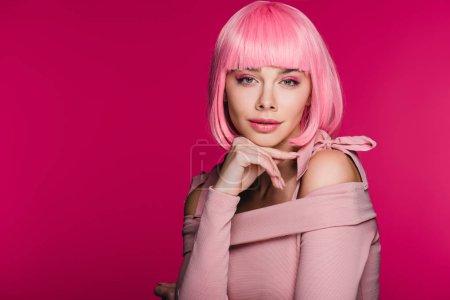 élégante charmante fille posant dans une perruque rose, isolée sur Rose
