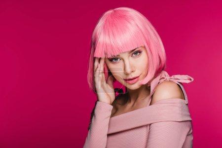 femme à la mode qui pose en perruque rose, isolé sur Rose