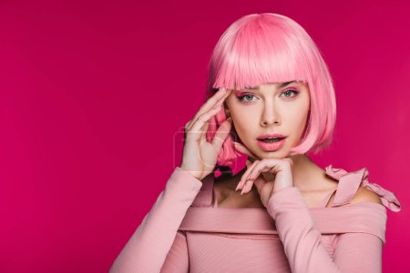 Photo for Beautiful fashionable girl gesturing and posing in pink wig, isolated on pink - Royalty Free Image