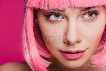 Photo pour Jolie fille posant dans une perruque rose, isolée sur Rose - image libre de droit