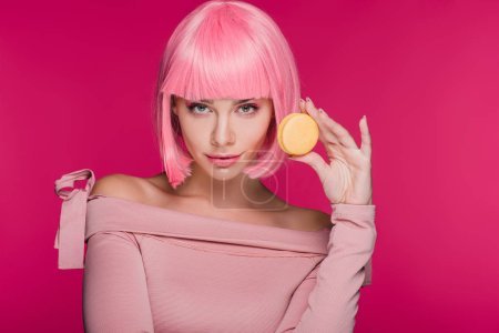 beautiful girl in pink wig posing with sweet macaron isolated on pink