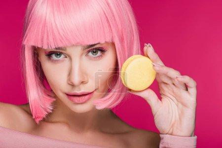 Photo pour Belle jeune femme à perruque rose posant avec macaron jaune isolé sur Rose - image libre de droit