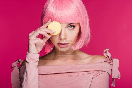 Photo for Young fashionable woman in pink wig posing with macaron isolated on pink - Royalty Free Image