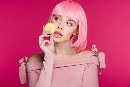 fashionable woman in pink wig posing with macaron isolated on pink