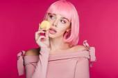 """Постер, картина, фотообои """"модная женщина позирует с macaron, изолированные на розовый розовый парик"""""""