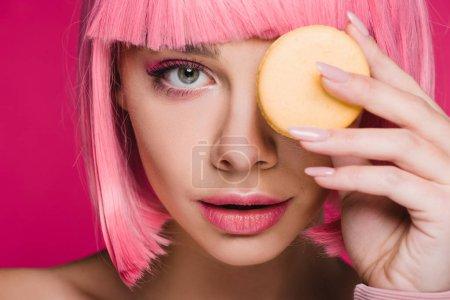 Photo pour Jolie fille en perruque rose posant avec macaron jaune isolé sur Rose - image libre de droit