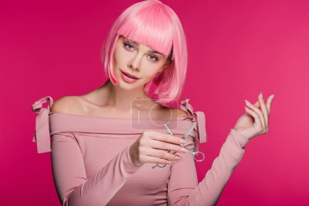 fashionable girl in pink wig holding scissors isolated on pink