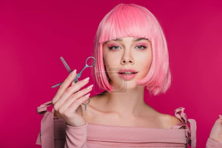 beautiful stylish girl in pink wig holding scissors isolated on pink