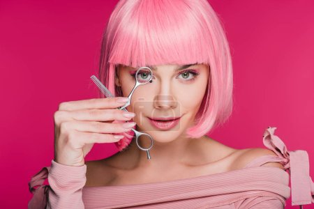 sensual girl with pink hairstyle looking through scissors isolated on pink