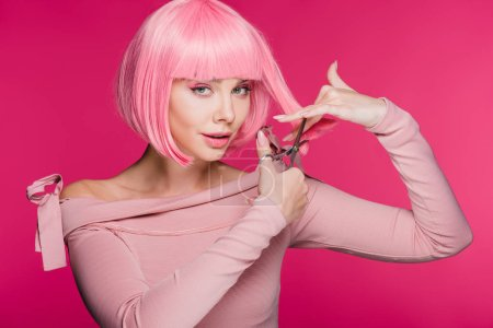 attractive girl cutting pink hair with scissors isolated on pink
