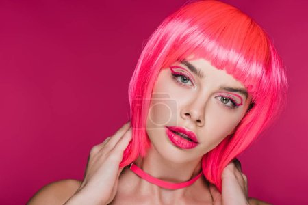 glamor model with fashionable makeup posing in neon pink wig, isolated on pink