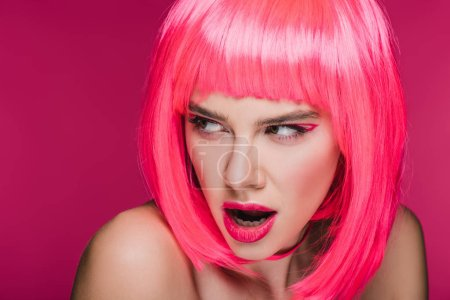 attractive surprised girl posing in neon pink wig, isolated on pink
