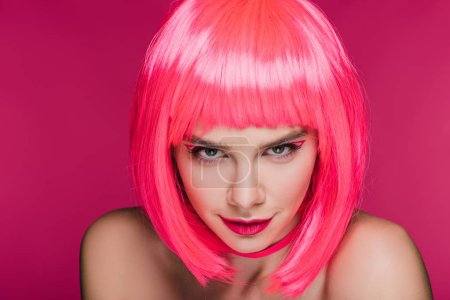Photo for Beautiful sly girl in neon pink wig looking at camera, isolated on pink - Royalty Free Image