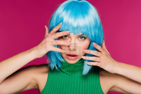 beautiful young woman gesturing and posing in blue wig, isolated on pink