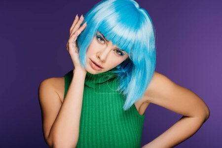 beautiful young woman gesturing and posing in blue wig, isolated on purple