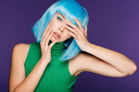 attractive sensual girl gesturing and posing in blue wig, isolated on purple